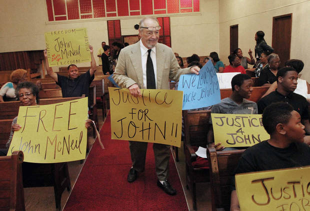 In this Oct. 3, 2012 photo, Bob Zellner, civil rights activist and author, hands out banners at the Freedom for John McNeil vigil held Wednesday evening at Holy Calvary Church,in Wilson, N.C.. John McNeil has been incarcerated in Georgia prisons for over 5 years for reportedly shooting an advancing trespasser at the McNeil family home in Cobb County, Georgia.(AP Photo/The Wilson Times, Gray Whitley)