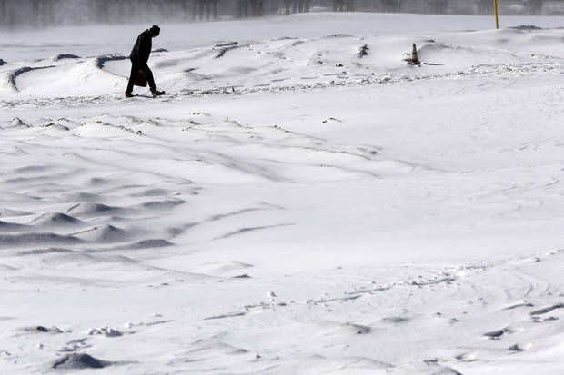 A man hunches over to protect himself from the wind and blowing snow while walking on the beach at New York's Coney Island, Saturday, Feb. 9, 2013.  A behemoth storm packing hurricane-force wind gusts and blizzard conditions swept through the Northeast overnight.  (AP Photo/Mary Altaffer) ORG XMIT: NYMA101