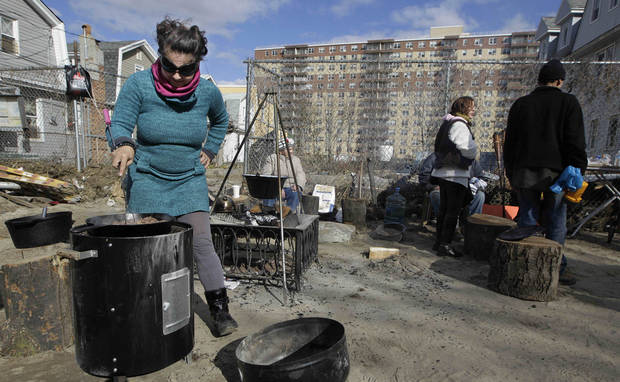 Kiva Kahl prepares beef stew for friends and neighbors in front of her residence in the Rockaways section of New York, Saturday, Nov. 3, 2012, in New York. More New Yorkers awoke Saturday to power being restored for the first time since Superstorm Sandy pummeled the region, but patience wore thin among those in the region who have been without power for most of the week.  (AP Photo/Kathy Willens) ORG XMIT: NYKW118