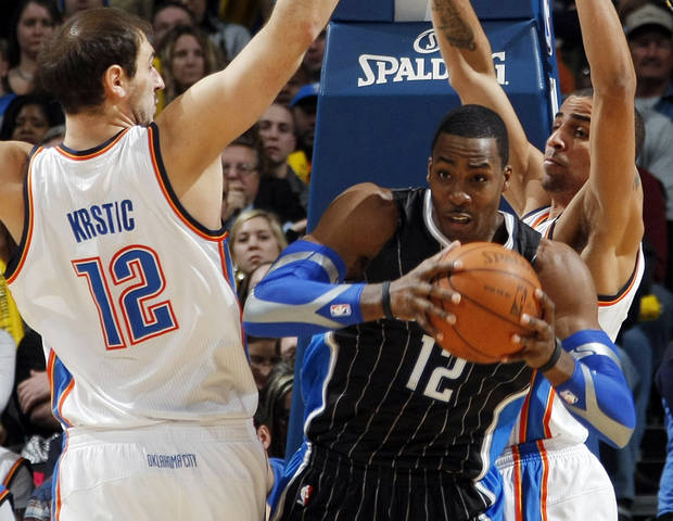Oklahoma City's Nenad Krstic (12) and Thabo Sefolosha (2) defend Orlando's Dwight Howard (12) during the NBA basketball game between the Orlando Magic and Oklahoma City Thunder in Oklahoma City, Thursday, January 13, 2011. Photo by Nate Billings, The Oklahoman