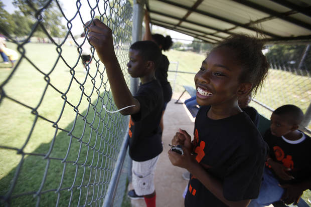 Meliyah Kinchion, 11, cheers from the dugout during a kickball tournament hosted by the Oklahoma City Police Department at South Rotary Park in Oklahoma City, Wednesday, June 27, 2012.  Photo by Garett Fisbeck, The Oklahoman