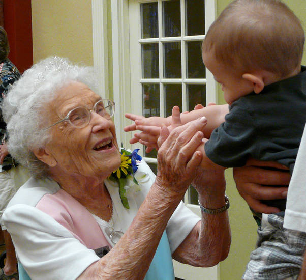Thelma Barnes reaches for Colin Townsend, 11 months, at her 104th birthday party Saturday at Rivermont Retirement Community in Norman. Barnes lives independently at the center and walks nearly a mile most days. PHOTO BY CONNIE HEFNER, FOR THE OKLAHOMAN