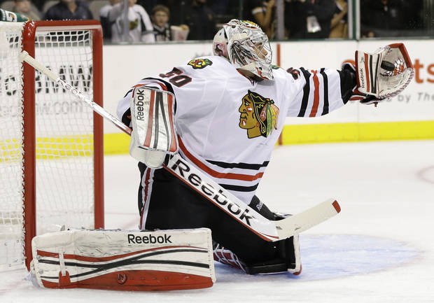 Chicago Blackhawks' Corey Crawford (50) reaches up to glove a shot from the Dallas Stars in the first period of an NHL hockey game, Thursday, Jan. 24, 2013, in Dallas. (AP Photo/Tony Gutierrez)