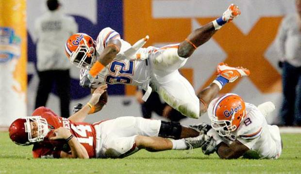 OU's Sam Bradford gets hit by Florida's Dustin Doe, center, and Carlos Dunlap during the second half of the BCS National Championship college football game between the University of Oklahoma Sooners (OU) and the University of Florida Gators (UF) on Thursday, Jan. 8, 2009, at Dolphin Stadium in Miami Gardens, Fla.   PHOTO BY BRYAN TERRY, THE OKLAHOMAN