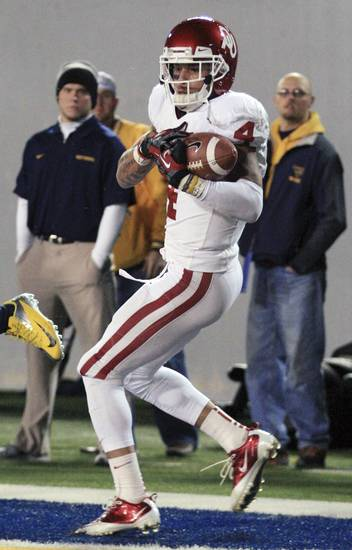 Oklahoma's Kenny Stills (4) catches a pass for a touchdown during the second quarter of their NCAA college football game against West Virginia in Morgantown, W.Va., on Saturday, Nov. 17, 2012. (AP Photo/Christopher Jackson)