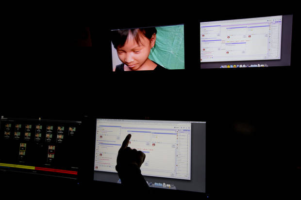 A Terre des Hommes researcher points to one of the chat sessions in a public chat room where users try and contact purported 10-year-old Sweetie from the Philippines, upper left in a computer-generated image, during a media opportunity in Amsterdam, Netherlands, Monday Nov. 4, 2013. The Dutch children's rights organization is warning of an epidemic of children being paid to perform sexual acts via webcams and is urging police and politicians around the world to crack down on the practice. Terre des Hommes, a Dutch-based organization that battles to stop child exploitation around the world, said Monday that to gauge the scale of the problem it created a fake 10-year-old  girl called Sweetie and she was bombarded with online offers to pay for webcam sex shows by child predators from around the world. (AP Photo/Peter Dejong)