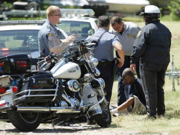 Oklahoma City police take a man into custody after a chase near NW 10 and Doris Drive on Wednesday. A police spokesman said the man was bitten in the face by a police dog as he hid beneath a tarp. Photo by Steve Gooch, The Oklahoman <strong>Steve Gooch</strong>