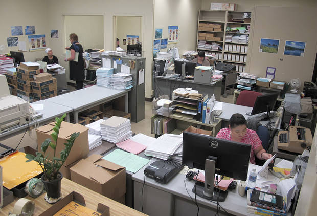 In this Feb. 20, 2013 photo, payroll clerks manually calculate payroll at the state of Hawaii's payroll office in Honolulu. Hawaii is moving to modernize and overhaul outdated technology _ like a paper-based payroll system and decades old VAX machine kept alive with parts from eBay _ that breeds inefficiency and creates opportunities for abuse and costly mistakes. (AP Photo/Audrey McAvoy)