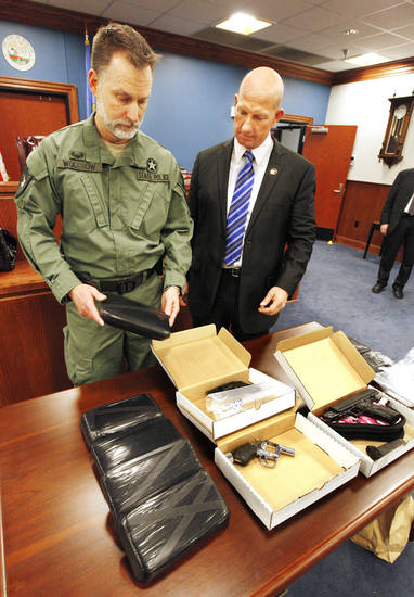 Mel Woodrow and Darrell Weaver, both with the Oklahoma Bureau of Narcotics and Dangerous Drugs Control, look at methamphetamine  and guns at the Bethany Police Department on Wednesday. The drugs were seized Wednesday in the Oklahoma City metro area. Photo by Paul B. Southerland, The Oklahoman <strong>PAUL B. SOUTHERLAND</strong>