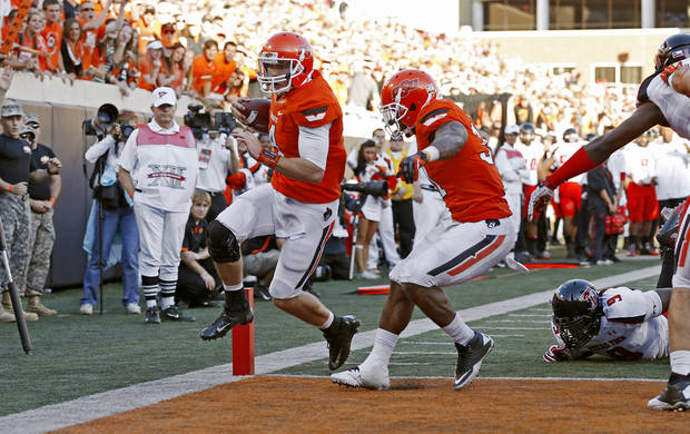 Oklahoma State&#039;s J.W. Walsh (4) scores a touchdown beside Jeremy Smith (31) during a college football game between Oklahoma State University (OSU) and Texas Tech University (TTU) at Boone Pickens Stadium in Stillwater, Okla., Saturday, Nov. 17, 2012.  Photo by Bryan Terry, The Oklahoman