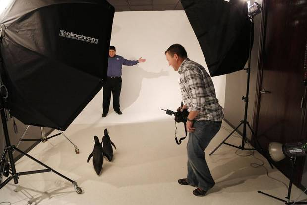 Photographer Chris Landsberger smiles as Magellanic penguins Penny and Pete follow SeaWorld animal ambassador Clay Carabajal into the studio as SeaWorld visited the OPUBCO on Thursday, Feb. 21, 2013, in Oklahoma City, Okla. Photo by Doug Hoke, The Oklahoman