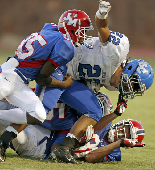 Bridge Creek's Loren Burrage fights off  John Marshall's Isiah Wade, left, and Tyler Stamm during a high school football game at Taft Stadium in Oklahoma City, Thursday, September 6, 2012. Photo by Bryan Terry, The Oklahoman