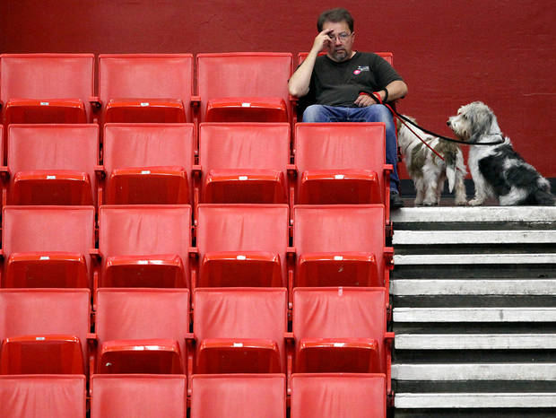 Steve Belflower, of Oklahoma City, watches part of the Oklahoma City Summer Classic Dog Show with his dogs Lucky (right) and Betty, at the Cox Convention Center in Oklahoma City Sunday, June 28, 2009. Photo by John Clanton, The Oklahoman