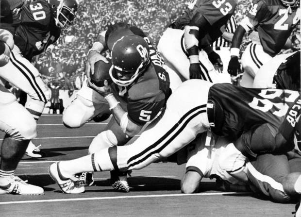 """Sooner quarterback Steve Davis lunges into the end zone for the first of his two one-yard touchdowns."" Staff photo by Hank Mooney taken 11/17/73; photo ran in the 11/18/73 Daily Oklahoman.    University of Oklahoma Sooners defeated the Kansas Jayhawks by a 48-20 score in Norman on Saturday, 11/17/73. File:  College Football/OU/OU-Kansas/Steve Davis/1973"