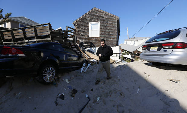 New Jersey State Assemblyman Vincent Prieto walks between homes damaged by Superstorm Sandy, Thursday, Nov. 29, 2012, in Normandy Beach, N.J. The New Jersey General Assembly took a tour of areas hit a month after the storm. (AP Photo/Julio Cortez)
