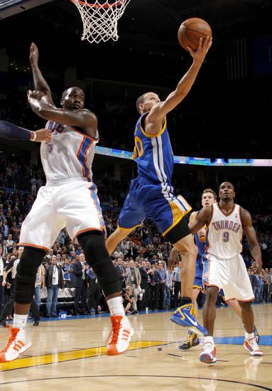 Golden State's Stephen Curry (30) goes to the basket between Oklahoma City's Kendrick Perkins (5) and Oklahoma City's Serge Ibaka (9) during the NBA basketball game between the Oklahoma City Thunder and the Golden State Warriors at the Oklahoma City Arena, Tuesday, March 29, 2011. Photo by Bryan Terry, The Oklahoman