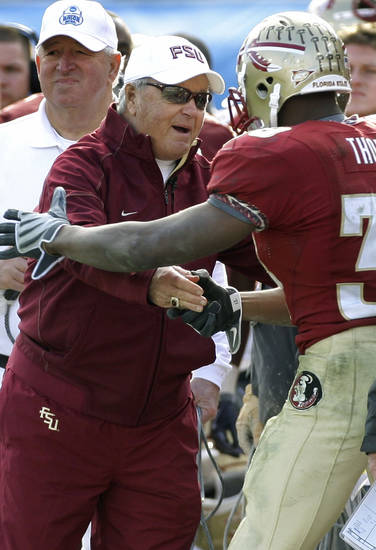 Florida State head coach Bobby Bowden, left, shakes hands with running back Jermaine Thomas during the third quarter of the Gator Bowl NCAA college football game against West Virginia after Thomas scored a touchdown, Friday, Jan. 1, 2010, in Jacksonville, Fla.  Florida State won 33-21, in Bowden's last game. (AP Photo/Phil Coale) ORG XMIT: FLPC219