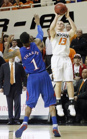 Oklahoma State 's Phil Forte (13) shoots the ball over Kansas' Naadir Tharpe (1) during the college basketball game between the Oklahoma State University Cowboys (OSU) and the University of Kanas Jayhawks (KU) at Gallagher-Iba Arena on Wednesday, Feb. 20, 2013, in Stillwater, Okla. Photo by Chris Landsberger, The Oklahoman