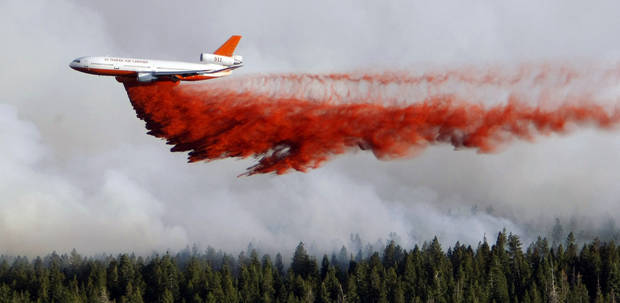 A heavy tanker drops retardant as crews battle the Shingle Fire east of Cedar City, Utah, on Monday, July 2, 2012. Evacuations were ordered as the 500-acre wildfire that broke out Sunday threatened about 100 cabins inside Dixie National Forest. In all, 10 wildfires were burning Monday across Utah. (AP Photo/The Deseret News, Scott G Winterton)