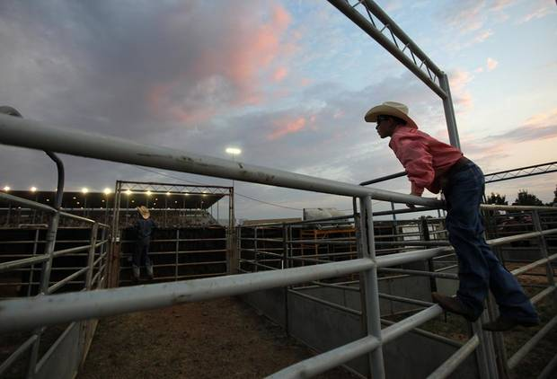 Seth Jackson, 11, of Bethel, Okla., watches a team roping event during International Finals Youth Rodeo in Shawnee, Okla., Sunday, July 8, 2012.  Photo by Garett Fisbeck, The Oklahoman
