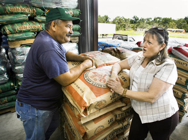 Melba Lee, manager of Lone Grove Feed and Supply, talks with customer Dick Elliott. The store was  damaged by the Feb. 10 tornado and reopened in August under new management.  PHOTOS BY BY STEVE SISNEY, THE OKLAHOMAN
