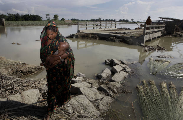 A woman carries her baby as she walks past a bridge that was washed away in the recent monsoon floods in Deeghal Ati village in northeastern Assam state, India, Sunday, July 8, 2012. About half of the 2.2 million people who were displaced remain in makeshift shelters or with relatives or friends. Villagers are still finding bodies in receding waters. On Sunday the death toll stood more than 120, including 16 buried in mudslides. (AP Photo/Anupam Nath)