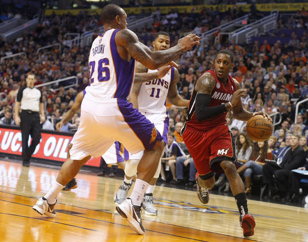 Miami Heat point guard Mario Chalmers (15) drives on Phoenix Suns point guard Shannon Brown (26) in the second quarter during an NBA basketball game on Saturday, Nov. 17, 2012, in Phoenix. (AP Photos/Rick Scuteri)