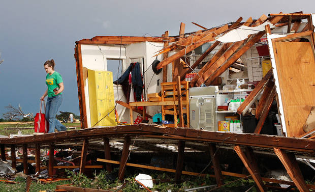 Rebecca Apel, 15, removes salvageable belongings from her family's home on SH 74 near Cashion  after a tornado ripped it apart late  Tuesday afternoon,  May 24, 2011, No one was inside the house; there were no injuries.   Photo by Jim Beckel, The Oklahoman