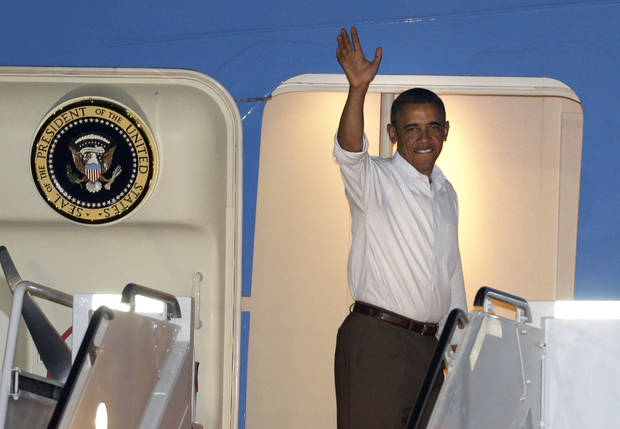 President Barack Obama waves as he boards Air Force One to return to Washington, at Honolulu Joint Base Pearl Harbor-Hickam in Honolulu, after spending Christmas with his family in Hawaii, Wednesday, Dec. 26, 2012. (AP Photo/Gerald Herbert)