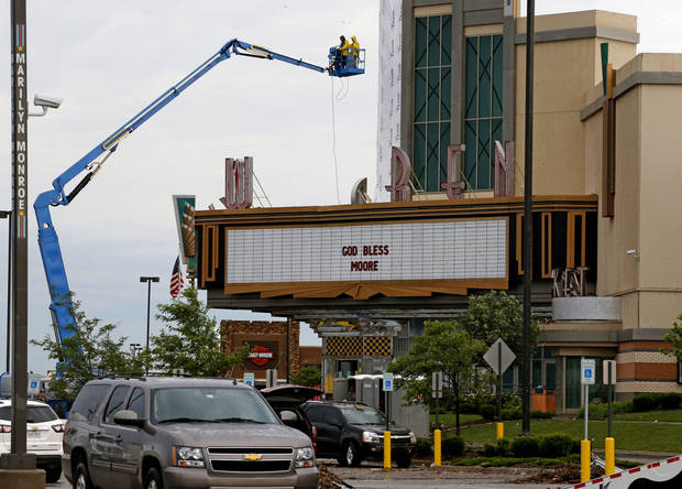 Workers begin to clean up the Warren Theatre in Moore on Tuesday. The theater has an estimated $500,000 to $1 million worth of damage. <strong>BRYAN TERRY - THE OKLAHOMAN</strong>