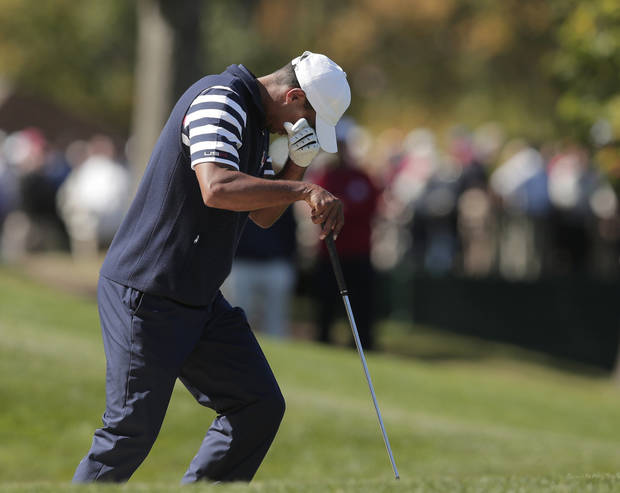 USA's Tiger Woods wipes his eyes after hitting out of a bunker on the second hole during a singles match at the Ryder Cup PGA golf tournament Sunday, Sept. 30, 2012, at the Medinah Country Club in Medinah, Ill. (AP Photo/Charlie Riedel)  ORG XMIT: PGA142