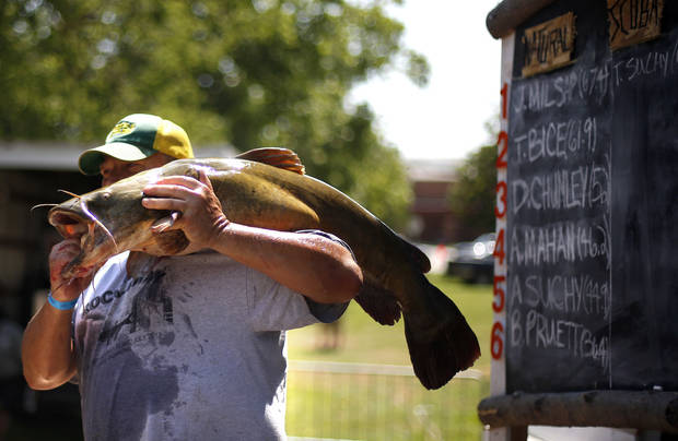 Mark McFarland, of Enid, Okla., holds his 36.1 pound catfish as he has his picture taken at the weigh-ins of the 14th annual Okie Noodling Tournament at Wacker Park in Pauls Valley, Okla., Saturday, June 22, 2013. Photo by Sarah Phipps, The Oklahoman