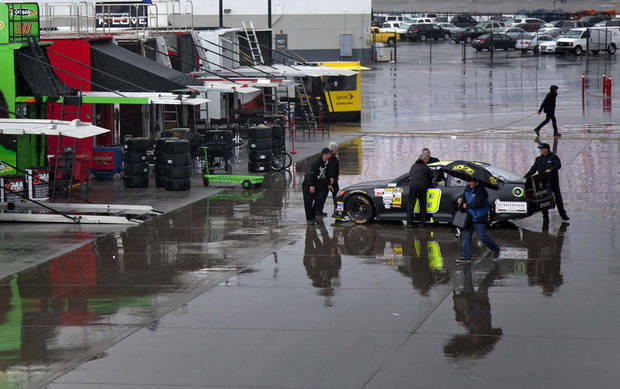 Pit crew members for Mike Bliss roll his Sprint Cup Series car out of the garage during a rain delay at Las Vegas Motor Speedway, Friday, March 8, 2013, in Las Vegas. Qualifying for Sunday's race was canceled because of rain. (AP Photo/Julie Jacobson)