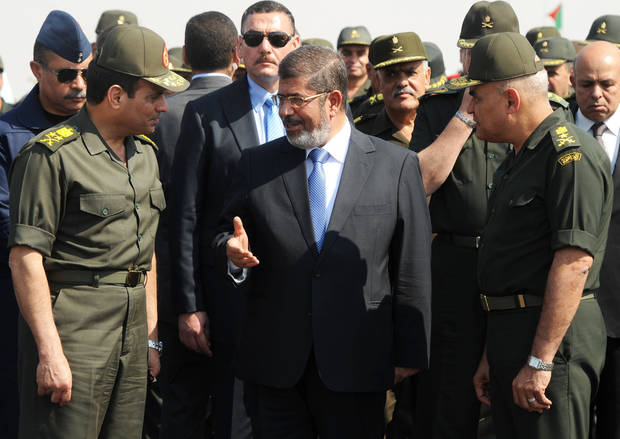 In this image released by the Egyptian Presidency, Egyptian President Mohammed Morsi, center, speaks with Minister of Defense, Lt. Gen. Abdel-Fattah el-Sissi, left, at a military base in Ismailia, Egypt, Wednesday, Oct. 10, 2012. (AP Photo/Egyptian Presidency)