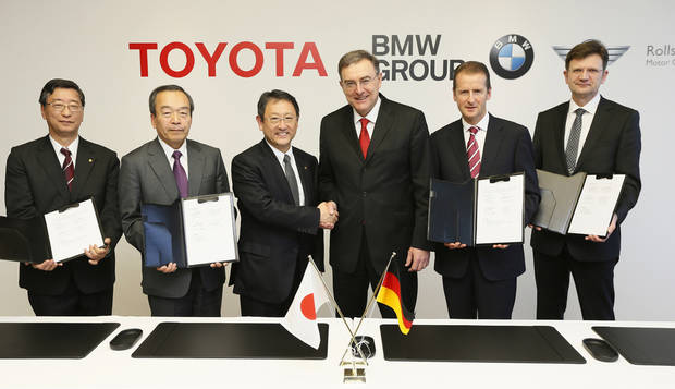 "In this photo released by Toyota Motor Corp., Toyota President Akio Toyoda, third left, shakes hands with BMW AG chief executive Norbert Reithofer, third right, as their executives show signed documents during a signing ceremony to jointly develop next-generation batteries for green vehicles in Nagoya, central Japan, Thursday, Jan. 24, 2013.  Toyota and BMW are working together on next-generation batteries for green vehicles called ""lithium-air"" as their collaboration, first announced in late 2011, moves ahead in fuel cells, sports vehicles and other fields. They are from left: Toyota's Director and Senior Managing Officer Yasumori Ihara, Toyota Executive Vice President Takeshi Uchiyamada, Toyoda, Reithofer, BMW AG board members, Herbert Diess and BMW Group Brand and Product Strategies Senior Vice President Klaus Frohlich. (AP Photo/Toyota Motor Corp.) EDITORIAL USE ONLY"