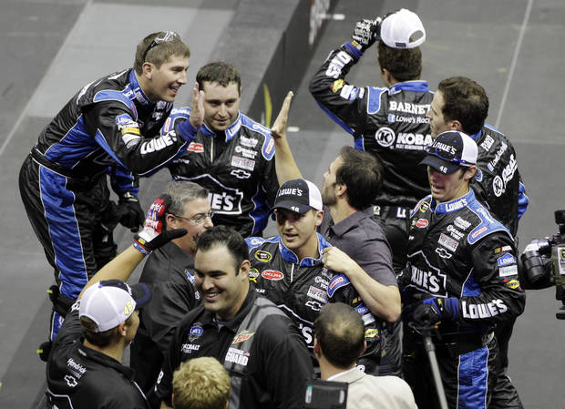 Crew members celebrate with driver Jimmie Johnson, right center, after winning the NASCAR Pit Crew Challenge in Charlotte, N.C., Thursday, May 17, 2012. (AP Photo/Chuck Burton)