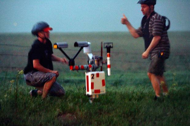 Isaac Hankes and research scientist Glen Romine from the University of Illinois deploy a second laser distrometer to measure particle size, rate, and direction (of raindrops) as members of VORTEX2 track an emerging super cell in central Oklahoma on Wednesday, May 13, 2009.  Less than a mile from deploying the first unit, the light falls to almost nothing, the rain comes in torrents, and they must now don head gear to protect from the quarter sized hail.  Photo by Steve Sisney, The Oklahoman