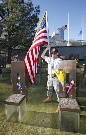 Retired Staff Sargent Ted Bryan Krey stands with a flag by the chairs of Sgt. Benjamin LaRanzo Davis and Capt. Randolph Guzman before the 18th Anniversary Remembrance Ceremony at the Oklahoma City National Memorial and Museum, Friday, April 19, 2013. Photo By David McDaniel/The Oklahoman