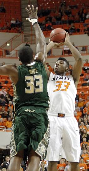 Oklahoma State 's Marcus Smart (33) shoots the ball over South Florida Bulls' Kore White (33) during the college basketball game between Oklahoma State University (OSU) and the University of South Florida (USF) on Wednesday , Dec. 5, 2012, in Stillwater, Okla.   Photo by Chris Landsberger, The Oklahoman