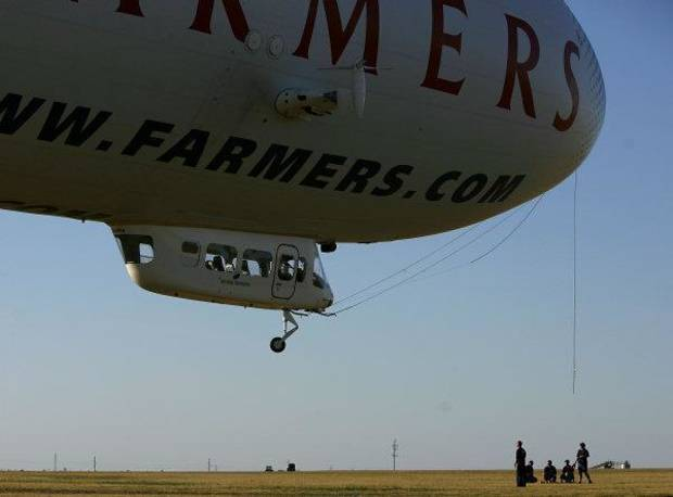 Crew members begin the masting process as The Farmers Airship lands at Wiley Post Airport in Oklahoma City on Monday, September 19, 2011. Photo by John Clanton, The Oklahoman ORG XMIT: KOD