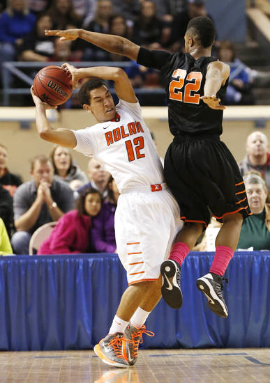 Douglass Trevon Threatt defends Roland's Seth Youngblood during the 4a boys championship game where the Douglass high school Trojans defeated the Roland Rangers 82-80 at the State Fair Arena on Saturday, March 9, 2013 in Oklahoma City, Okla.  Photo by Steve Sisney, The Oklahoman