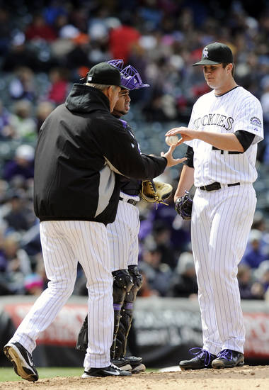 Colorado Rockies starting pitcher Drew Pomeranz hands the ball over to Colorado Rockies manager Jim Tracy in the fifth inning of a baseball game against the Arizona Diamondbacks on Sunday, April 15, 2012 in Denver. The Diamondbacks won 5-2. Colorado Rockies catcher Wilin Rosario is at center. (AP Photo/Chris Schneider)