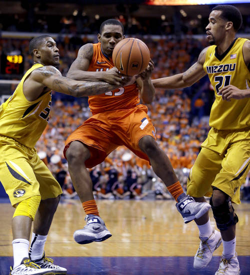 Illinois' Tracy Abrams, center, tries to control the ball as Missouri's Jabari Brown, left, and Laurence Bowers defend during the first half of an NCAA college basketball game Saturday, Dec. 22, 2012, in St. Louis. (AP Photo/Jeff Roberson)