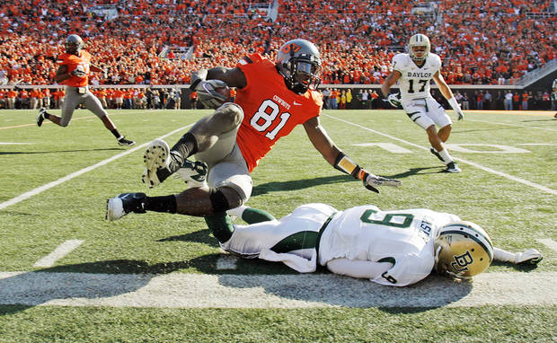 OSU's Justin Blackmon (81) collides with Baylor's Chance Casey (9) at the end of a long run after a catch in the second quarter during a college football game between the Oklahoma State University Cowboys (OSU) and the Baylor University Bears (BU) at Boone Pickens Stadium in Stillwater, Okla., Saturday, Oct. 29, 2011. Photo by Nate Billings, The Oklahoman
