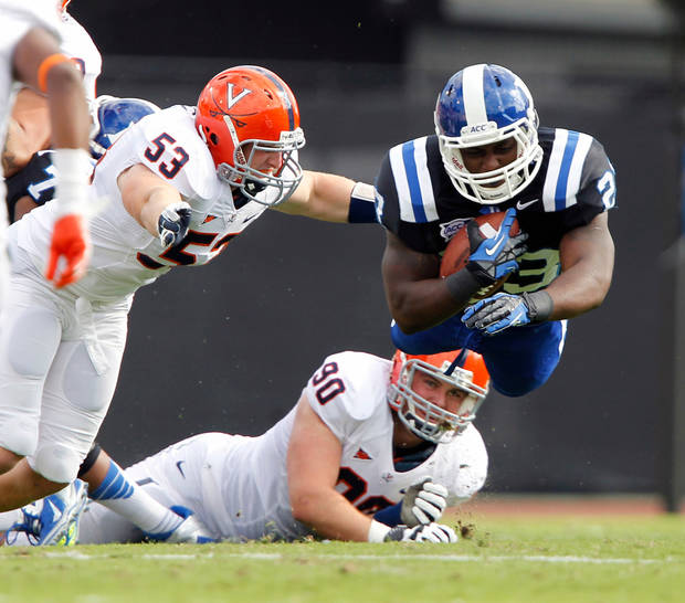 Duke running back Juwan Thompson (23) dives for yardage against Virginia defenders Steve Greer (53) and Jake Snyder (90) during the first quarter of an ACC college football in Durham N.C., on Saturday, Oct. 6, 2012. (AP Photo/The News & Observer, Chris Seward)