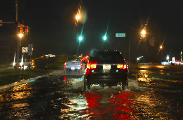 A car drives through high water on Council at I-40, Friday, May 31, 2013. Photo by David McDaniel, The Oklahoman