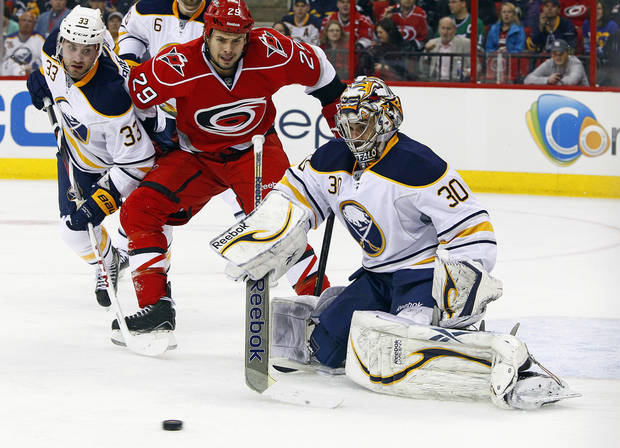 Buffalo Sabres goalie Ryan Miller (30) eyes the puck in front of a charging Carolina Hurricanes' Tim Wallace (29) and Sabres' T.J. Brennan (33) during the second period of an NHL hockey game, Tuesday, March 5, 2013, in Raleigh, N.C. (AP Photo/Karl B DeBlaker)