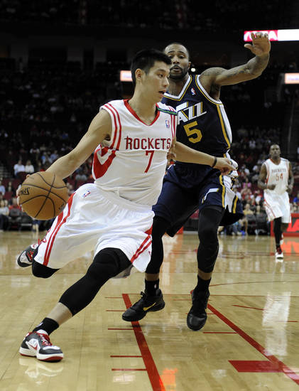 Houston Rockets' Jeremy Lin (7) drives the ball past Utah Jazz's Mo Williams (5) in the first half of an NBA basketball game on Saturday, Dec. 1, 2012, in Houston. (AP Photo/Pat Sullivan)