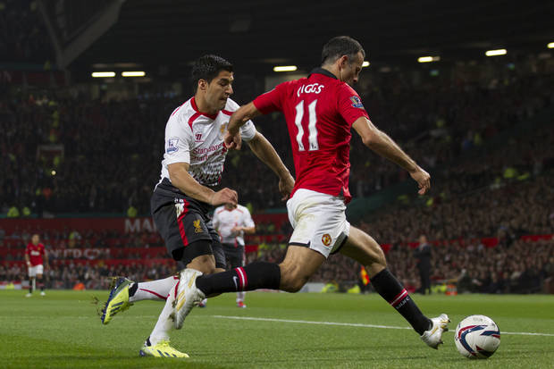 Manchester United's Ryan Giggs, right, keeps the ball from Liverpool's Luis Suarez during their English League Cup soccer match at Old Trafford Stadium, Manchester, England, Wednesday Sept. 25, 2013. (AP Photo/Jon Super)