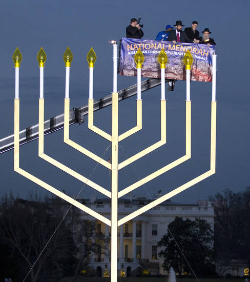 FILE - This Dec. 20, 2011 file photo shows Office of Management and Budget  Director Jacob Lew, second from right, Rabbi Levi Shemtov, second from left, and Rabbi Abraham Shemtov, right, as they light the National Hanukkah Menorah during a ceremony on The Ellipse in Washington marking the first night of Hanukkah. This year the National Menorah lighting event, sponsored by American Friends of Lubavitch, is scheduled to take place at the Ellipse outside the White House in Washington, D.C. at 4 p.m. on Sunday, Dec. 9, 2012. The eight-day Jewish holiday begins at sundown Saturday, Dec. 8.  (AP Photo/Manuel Balce Ceneta, file)